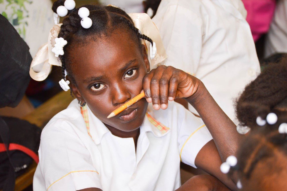 A young girl in a classroom holding a pencil under her nose