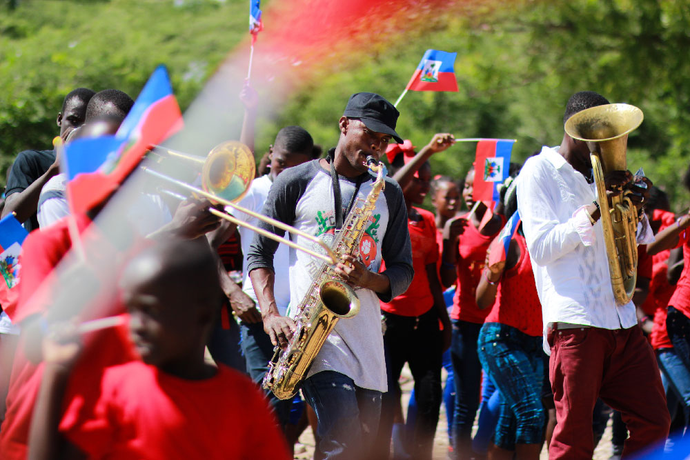 A man playing a saxophone in a parade in Haiti