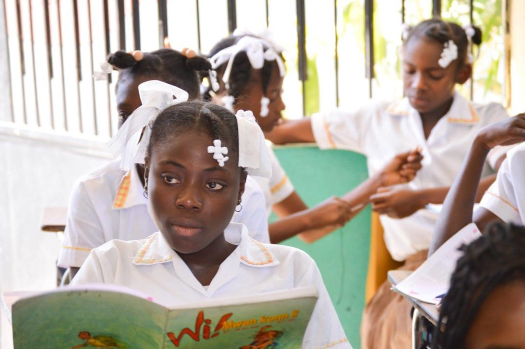 A Haitian girl in her classroom reading