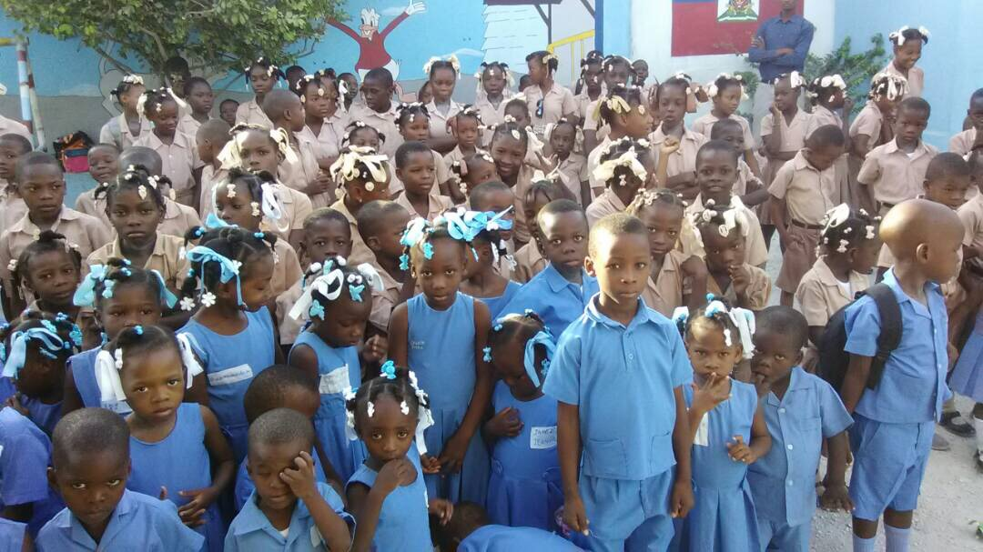 Large group of Haitian students standing outside of their school