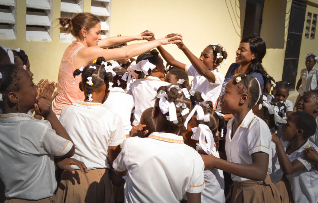 A woman joining hands with students at a Haitian school