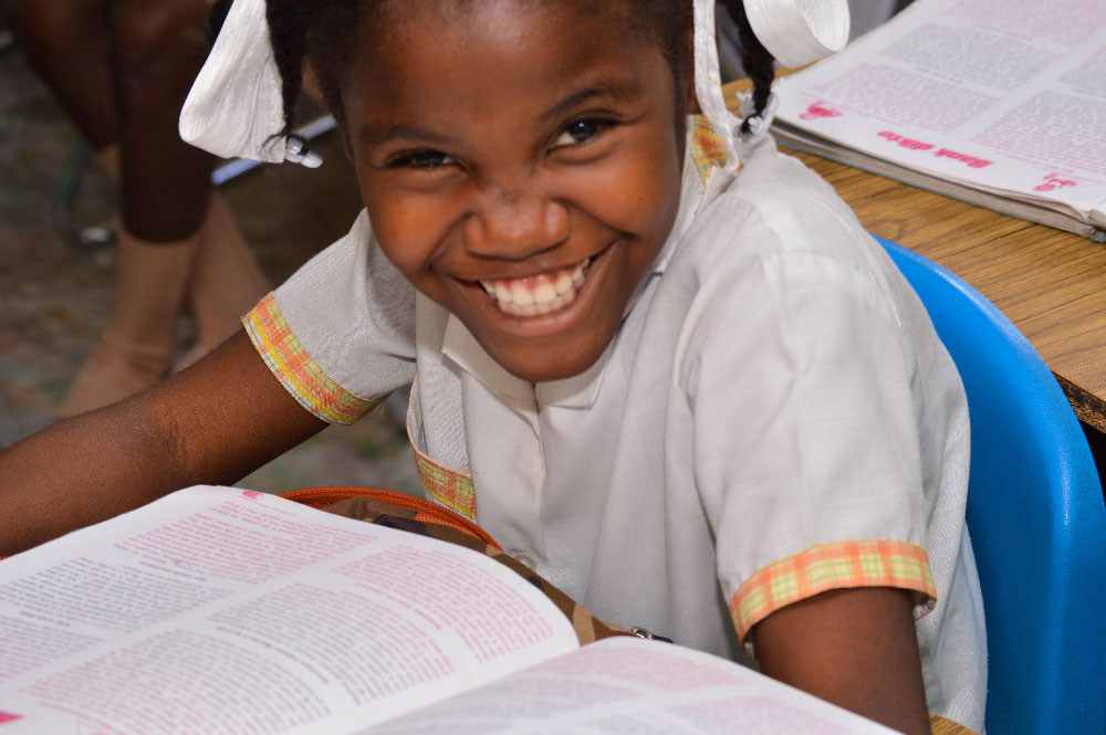 A young Haitian girl smiling while reading at her desk