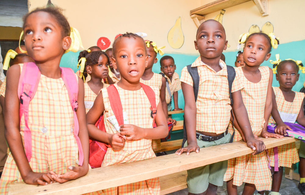 A classroom of Haitian students with backpacks on