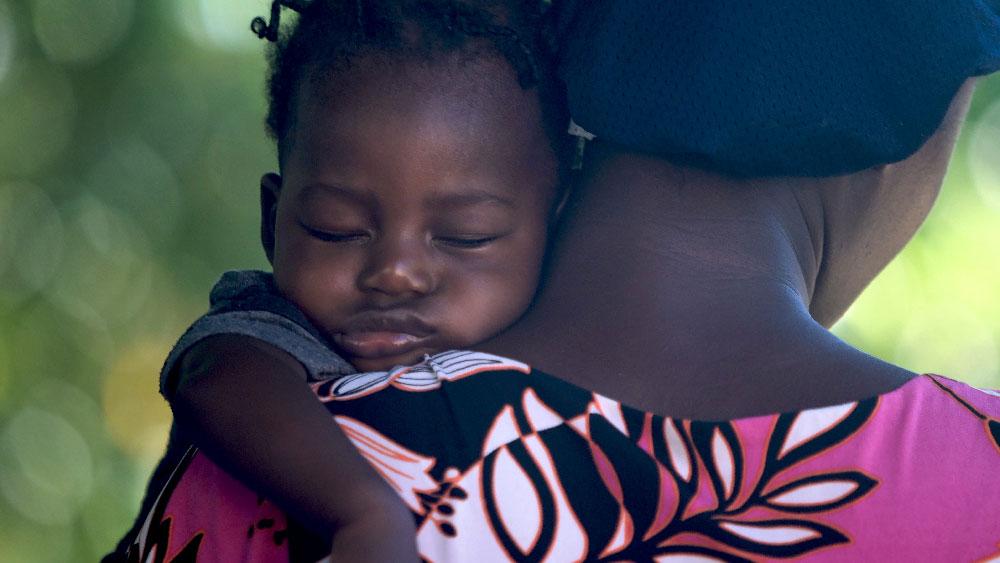 A toddler sleeping on her mother's shoulder