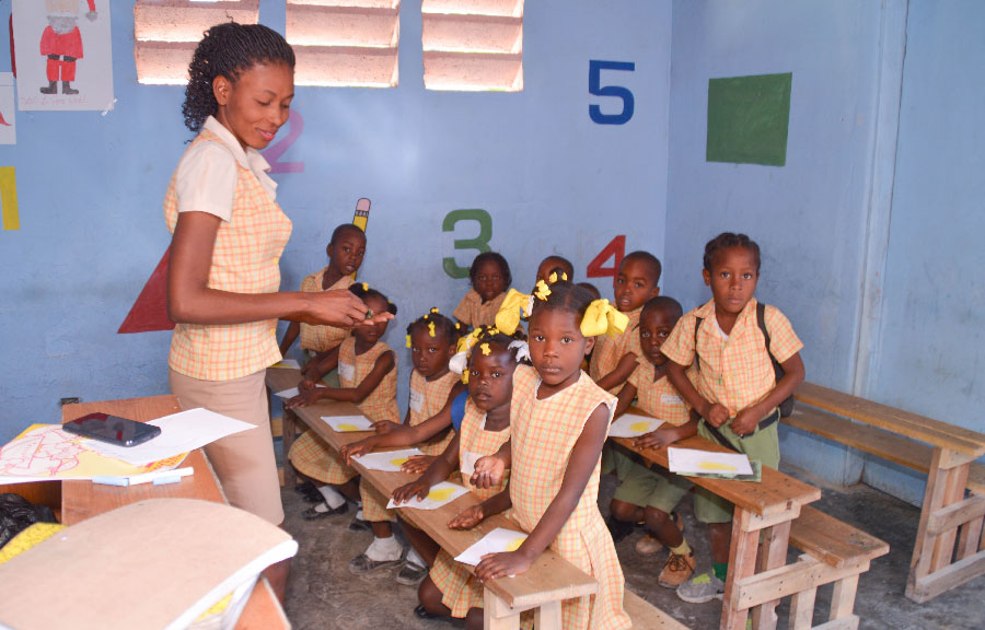 A group of young Haitian students with their teacher in the classroom