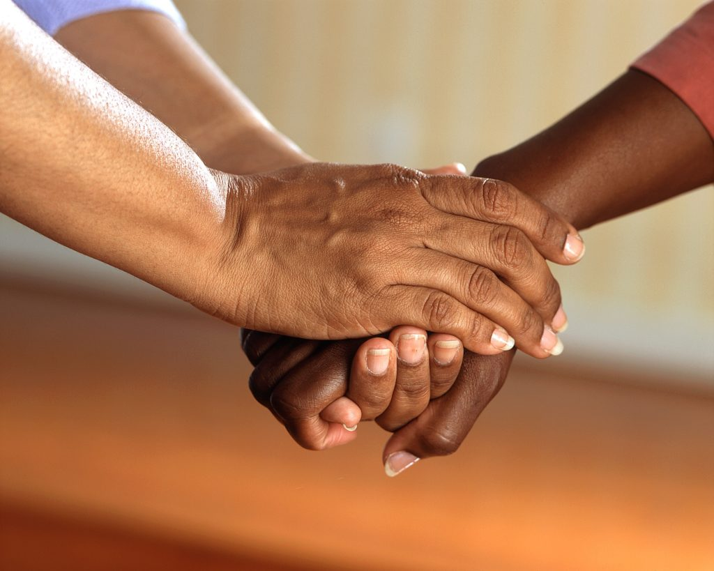 A caregiver holding the hand of another person