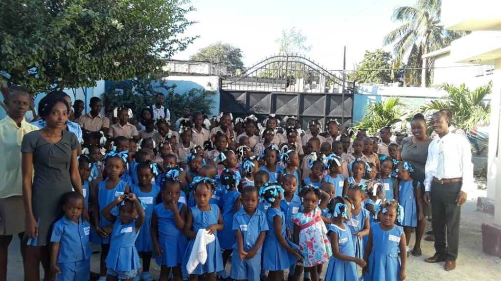 Students in Haiti posing with their teachers at the school gates